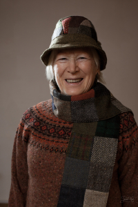 The woman in Patchwork Tweed Country Hat by Hanna Hats and Patch-brown Tweed Scarf by Hanna Hats