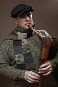 The man in Blue Sean Tweed Cap by Hanna Hats and  Patch-brown Tweed Scarf by Hanna Hats