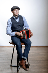 A man in a suit and cap with an accordion